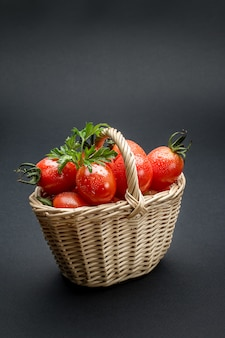 Tomatoes in a wicker basket on gray surface