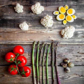 Tomatoes with asparagus, eggs, cauliflower top view on a dark wooden background