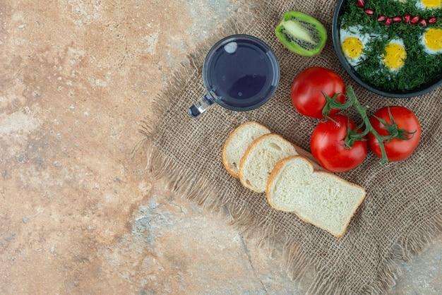 Помидоры с хлебом и чашка чая с омлетом.