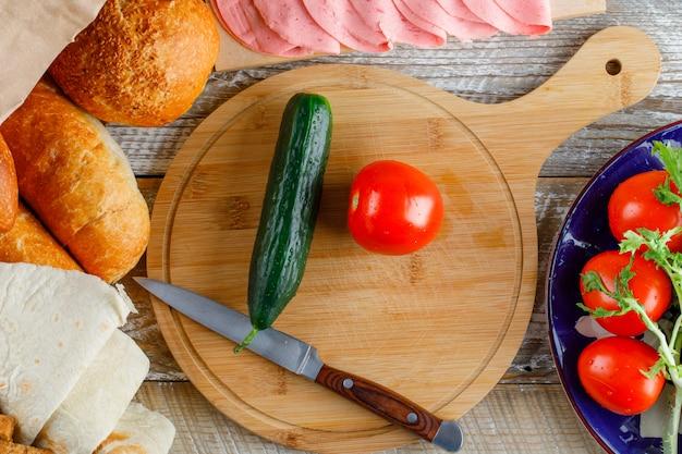 パン、キュウリ、ナイフ、ソーセージ、木の板とまな板、野菜のフラットトマト。