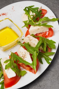 Tomatoes with cheese, arugula and honey. vertical frame