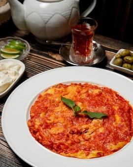 卵と熱いお茶のカップとトマト