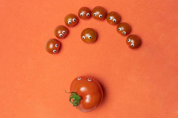 Tomatoes with eyes funny concept, copy space. fresh little cherry and big hothouse