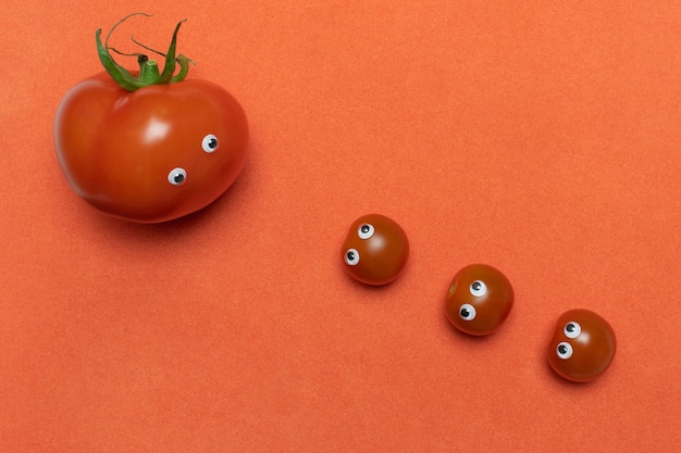 Tomatoes with eyes funny concept, copy space. three fresh little cherry