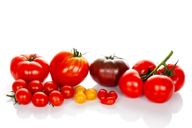 白い背景で隔離の緑の葉を持つトマト