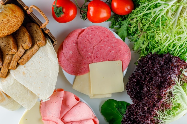 Tomatoes with leafy greens, red lettuce, bread, cheese, sausage flat lay