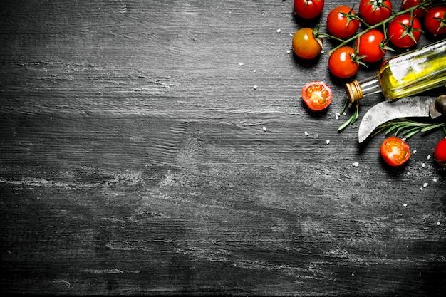 トマトとオリーブオイル。黒の素朴な背景に。