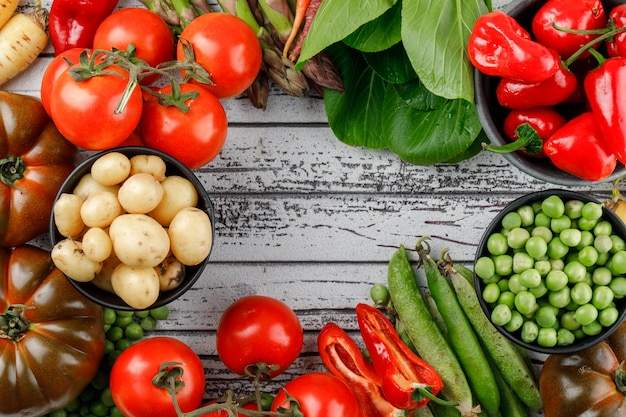 Tomatoes with peppers, potatoes, asparagus, sorrel, green pods, peas, carrots on wooden wall, flat lay.