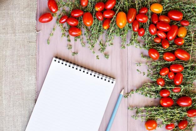 スパイスと木製のテーブルのレシピ本とトマト。上面図。