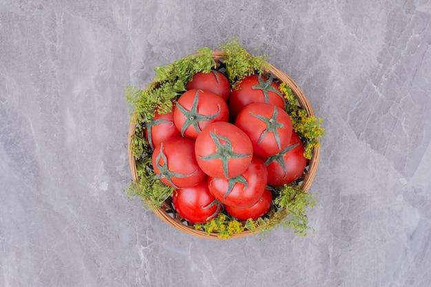 Pomodori in una tazza di legno con erbe intorno.