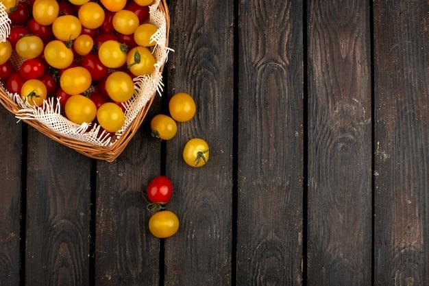 Canestro interno maturo fresco giallo e rosso dei pomodori sul pavimento rustico di legno