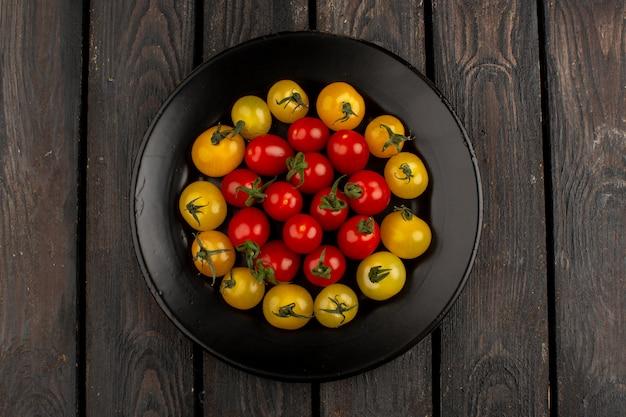 Banda nera interna a forma di rotonda gialla e rossa dei pomodori su un rustico