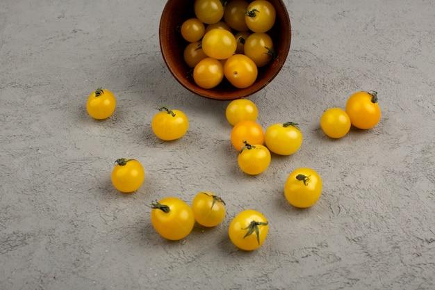 Pomodori gialli maturi freschi dentro e fuori del vaso rotondo marrone sul grigio