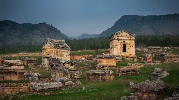 산의 배경에 터키 파묵칼레에있는 히 에라 폴리스의 고대 도시에있는 무덤