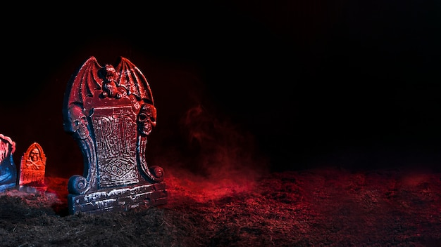 Tombstones illuminated by red light on soil
