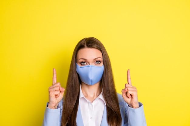 내일 자가격리. 의료용 마스크를 쓴 진지한 여성 수석 여성은 검지 손가락 카피스페이스를 가리키며 밝은 색 배경 위에 격리된 파란색 재킷 슈트를 입는 코비드 뉴스 광고를 보여줍니다.