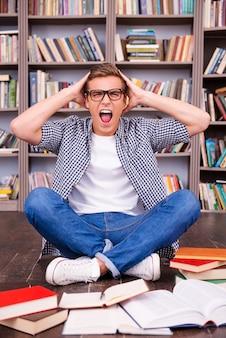 明日は私の最終試験です!ショックを受けた若い男が手で頭に触れ、本棚に座って叫ぶ