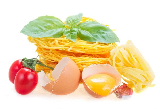 白地に分離された卵とトマトのトナレリ生パスタ