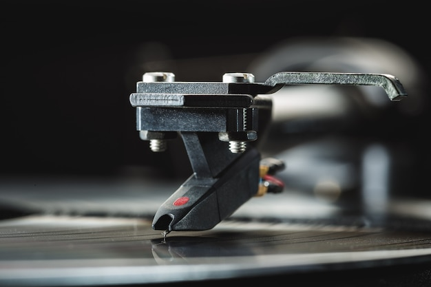 Tonearm with background cartridge for vinyl records. close-up, copy space.