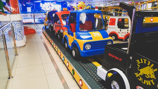 Тонированное фото крупным планом красочного поезда с тележкой, похожей на автомобили, для детей в тематическом парке развлечений