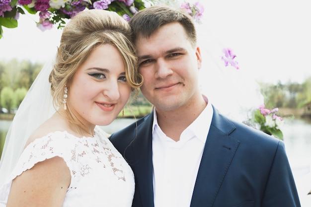 Toned closeup portrait of elegant bride and groom at wedding ceremony