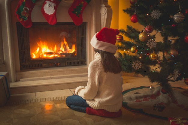Toned image of beautiful girl in santa hat sitting on floor and looking at fireplace