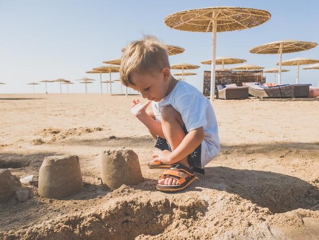 모래 해변에 앉아 젖은 모래에서 성을 짓고 사랑스러운 유아 소년의 톤된 이미지