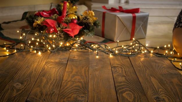 Тонированное изображение пустого деревянного стола на фоне подарков, светящихся огней и елки