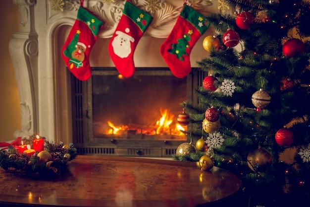 장식된 벽난로와 크리스마스 트리 앞의 빈 나무 테이블의 톤된 이미지. 텍스트에 대 한 장소입니다. 크리스마스 배경에 적합합니다.