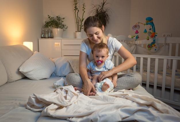 아기에게 기저귀를 갈아주는 엄마의 몸매 이미지