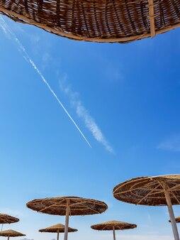 青い空と明るい空を背景に海のビーチで傘のシルエットのトーンのイメージ