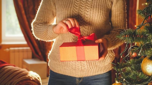 Тонированное изображение молодой женщины, разворачивающей и открывающей рождественскую подарочную коробку