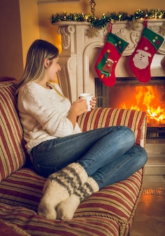 Toned image of young beautiful woman in woolen socks relaxing on sofa at burning fireplace and drinking tea