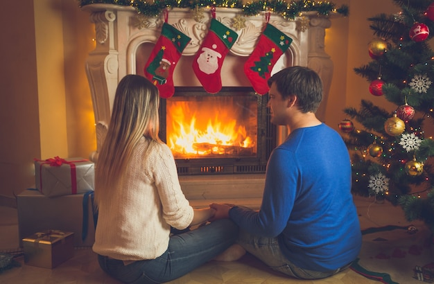 Toned image of young couple in love sitting by the fireplace decorated or christmas and looking at fire