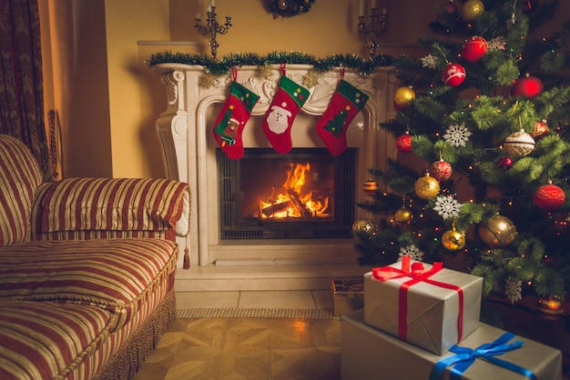 Toned interior photo of living room with burning fireplace, decorated christmas tree and stack of gifts