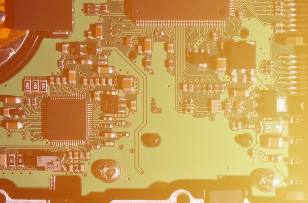 A toned macro image of a computer board with many small technological elements.