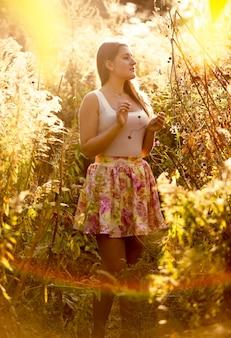 Toned photo of beautiful woman walking at field at sunset