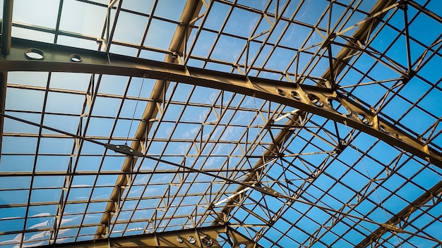 Toned photo of big glass roof on old railway station at bright sunny day