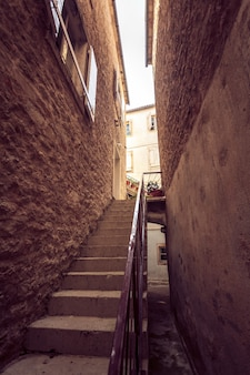 Toned photo of big stairway at old narrow street