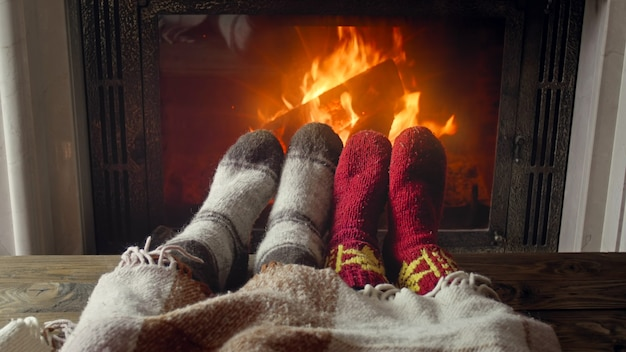 Toned photo of couple feet wearing warm socks lying under blanket by the burning fireplace