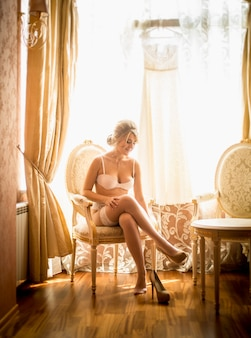Toned photo of elegant bride getting dressed at hotel room against big window