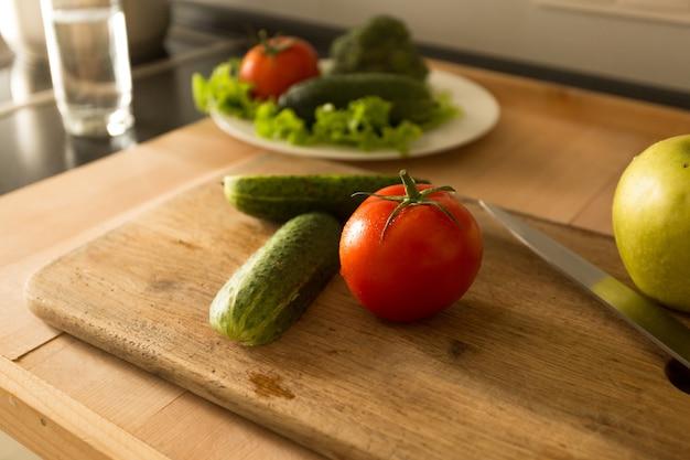 キッチンで木の板の上に横たわっている野菜や果物の上からのトーンの写真