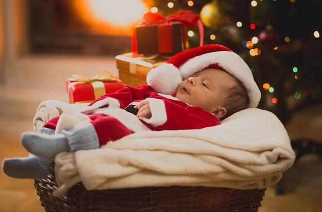Тонированное фото мальчика в костюме санта-клауса, спящего в гостиной у камина
