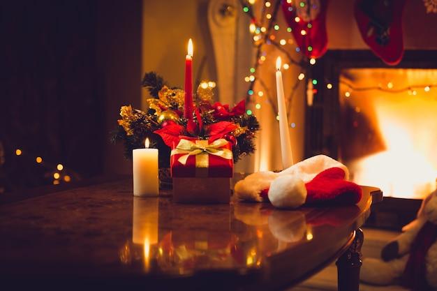 Тонированное фото горящих свечей, камина и подарочной коробки в канун рождества