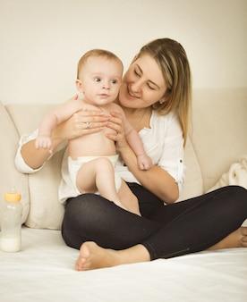 침대에서 6 개월 아기와 함께 포즈를 취하는 쾌활한 젊은 어머니의 몸매 사진