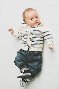 침대에 누워 청바지와 스웨터에 귀여운 아기의 몸매 사진