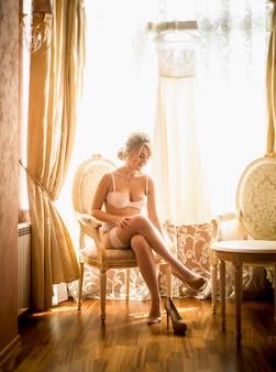 大きな窓に対してホテルの部屋で服を着るエレガントな花嫁のトーンの写真