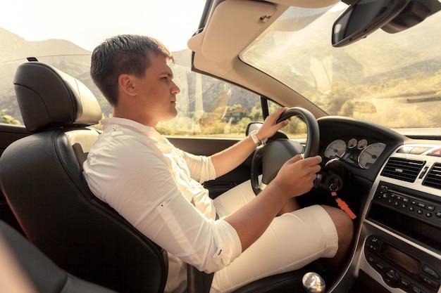 화창한 날에 컨버터블을 운전하는 잘 생긴 젊은 남자의 몸매 사진