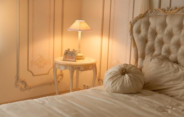 ベッドサイド テーブルにランプが付いている豪華な寝室のトーンの写真