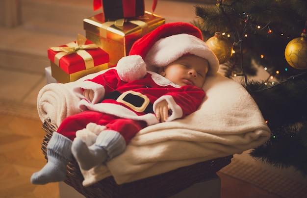 Тонированное фото новорожденного мальчика, одетого в костюм санта-клауса, лежащего с рождественскими подарками